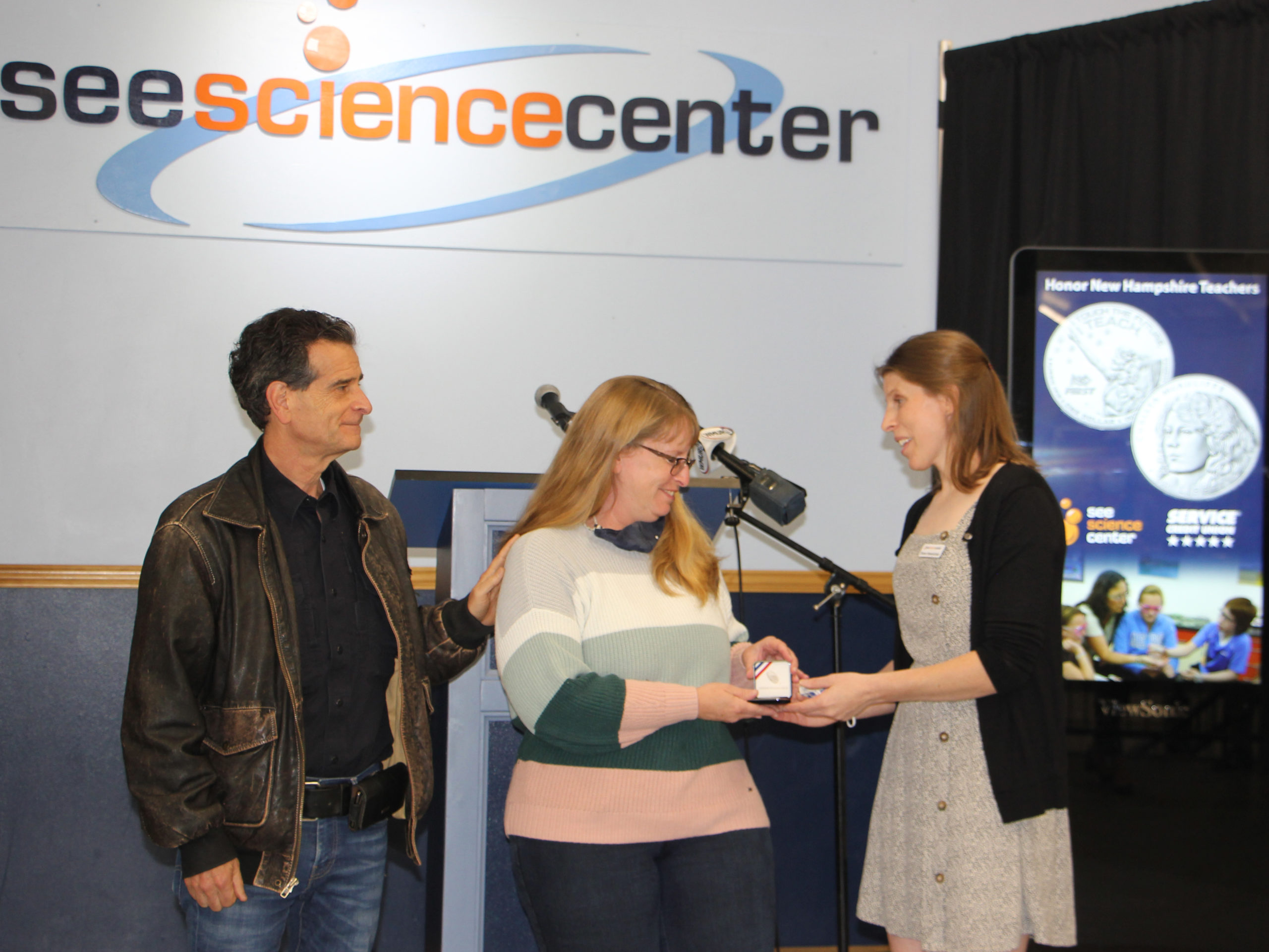 SEE Educator Becky Mayhew receives a coin from SEE director Shana Hawrylchak and Dean Kamen