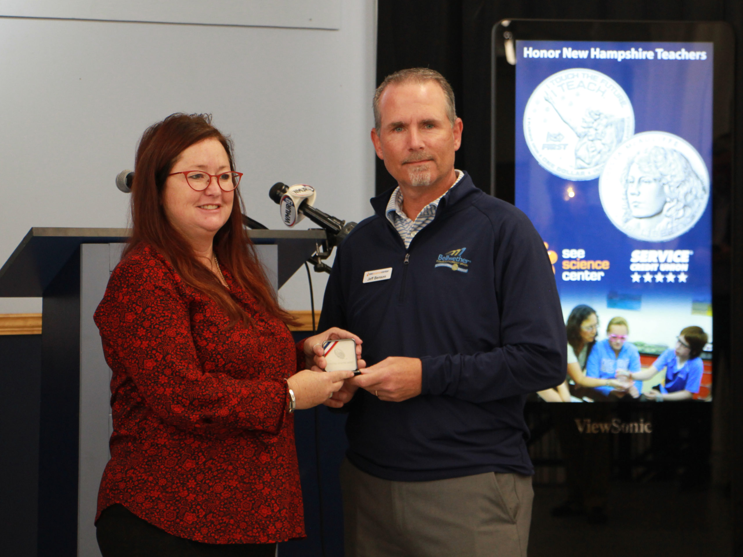 Assistant Manchester School District Superindendant Amy Allen receives coins for Manchester teachers from SEE board chair Jeff Benson